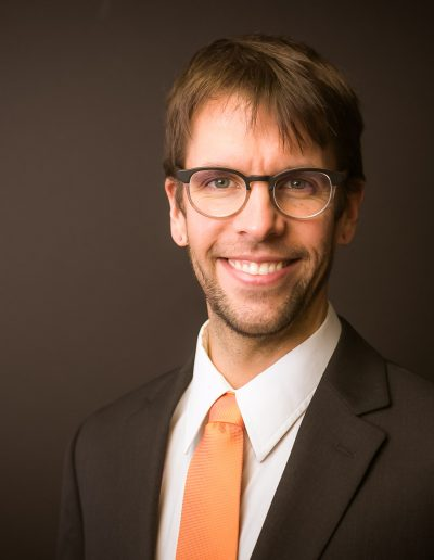 Professional gentleman with glasses in brown suit, white shirt and orange tie