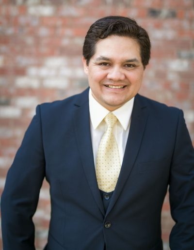 Man in dark blue suit and yellow tie smiling for headshot