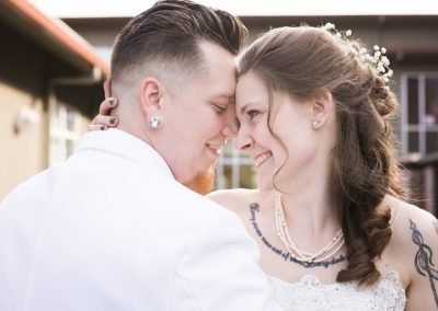 Husband and wife hug smiling face to face smiling after their Tacoma wedding