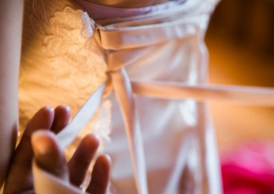 close up image of a brides wedding gown being tied