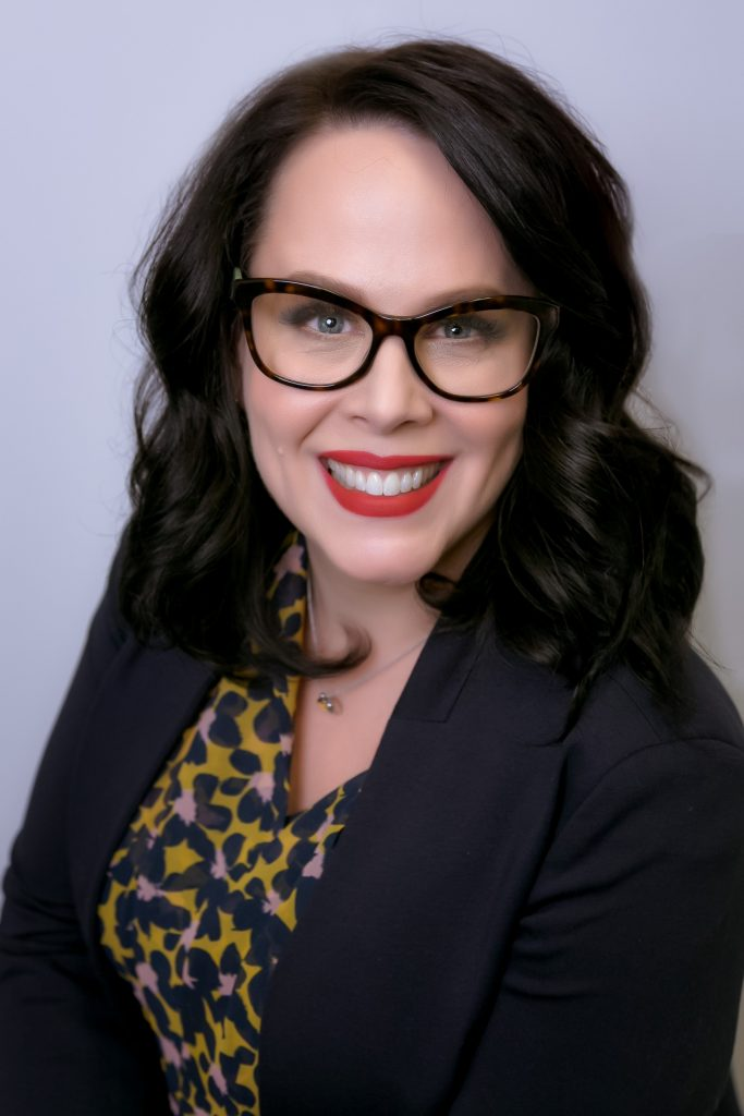 Smiling woman with red lipstick, dark brown hair and flower blouse