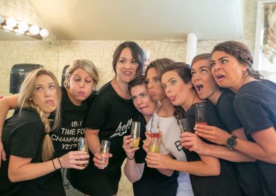 bachelorette party with bridesmaids holding mimosas, making silly faces, their arms around each other in a row