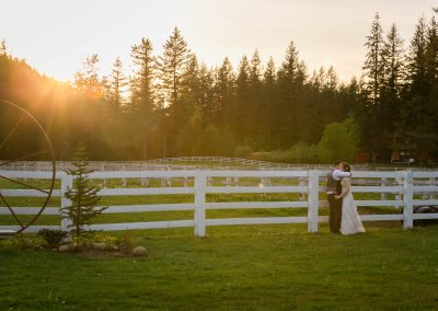 bride and groom hug after getting married on farm with evergreen trees and white fence