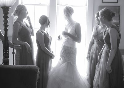 Bride and 4 bridesmaids looks out a Puyallup church window before wedding