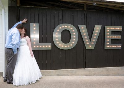 A newly wed husband and wife lean on wall with large letters spelling LOVE as they kiss in their wedding gown outfit
