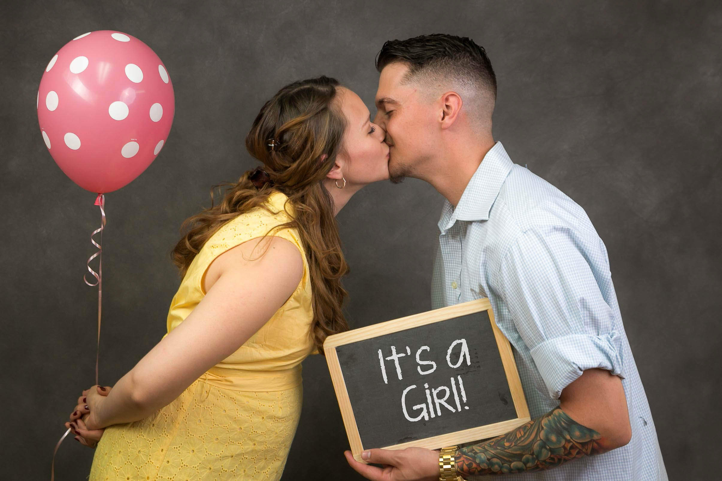"""Mom and Dad kissing. Holding pink spotted balloon and a """"it's a girl"""" chalkboard"""